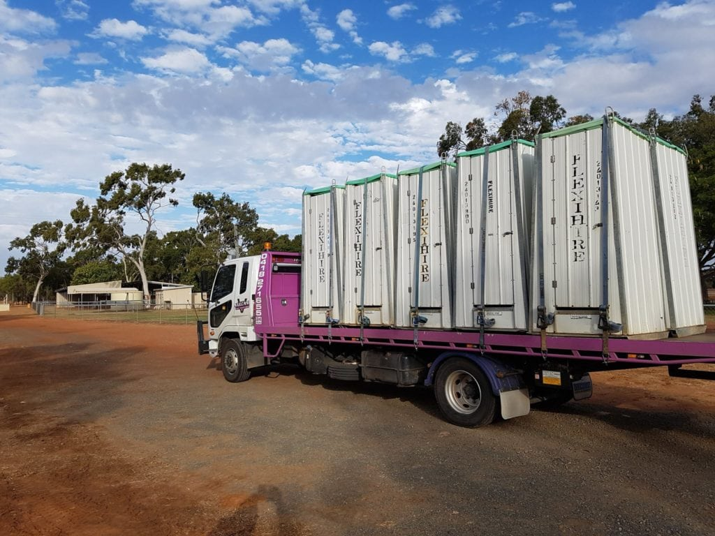 Vulcan truck transporting portable toilets